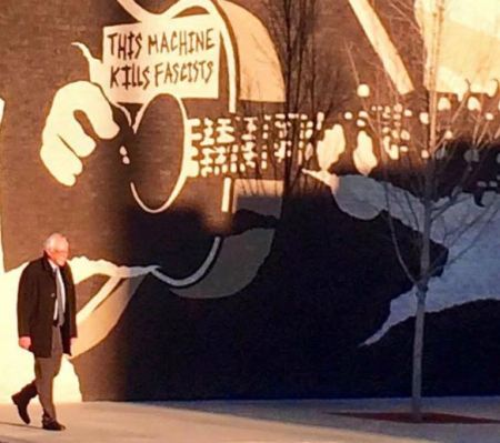 Bernie Sanders walks in front of Woody Guthrie mural - Tulsa, OK.